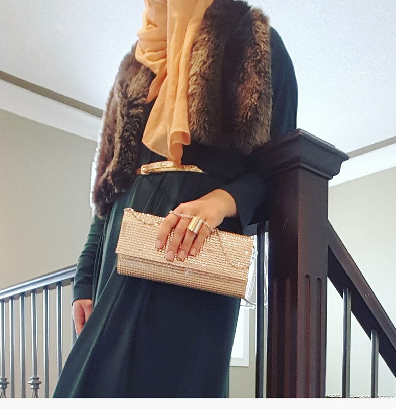 Faux fur scarf, a forest green maxi skirt with a gold belt and a gold clutch
